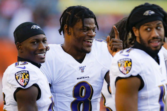 Baltimore Ravens quarterback Lamar Jackson, center, laughs on the sidelines during the second half of NFL football game against the Cincinnati Bengals, Sunday, Nov. 10, 2019, in Cincinnati. (AP Photo/Gary Landers)