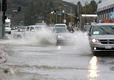 Drivers travel through deep water sitting on Sunland Boulevard, near the La Tuna Fire, in Los Angeles, California, U.S., March 22, 2018. REUTERS/Kyle Grillot