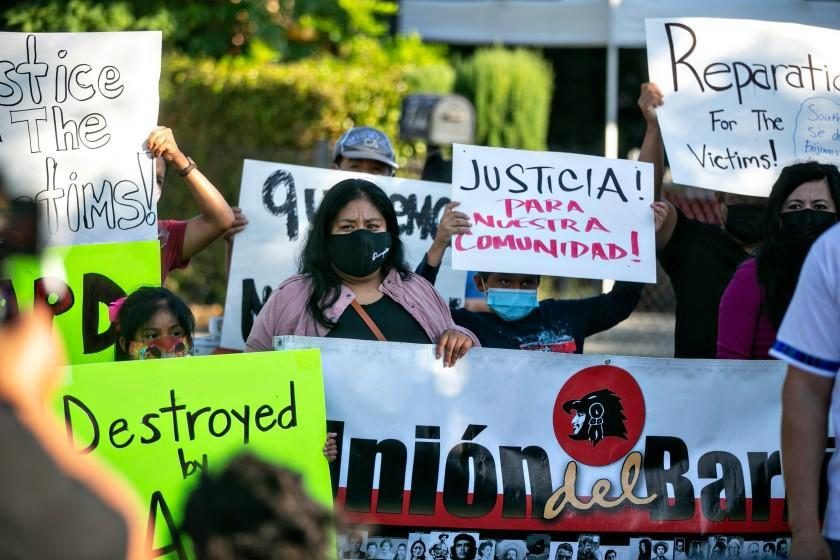LOS ANGELES, CA - SEPTEMBER 16: Community members hold a news conference in front of their homes to protest the city's handling of the June 30 LAPD fireworks explosion that damaged local homes on Thursday, Sept. 16, 2021 in Los Angeles, CA.(Jason Armond / Los Angeles Times)