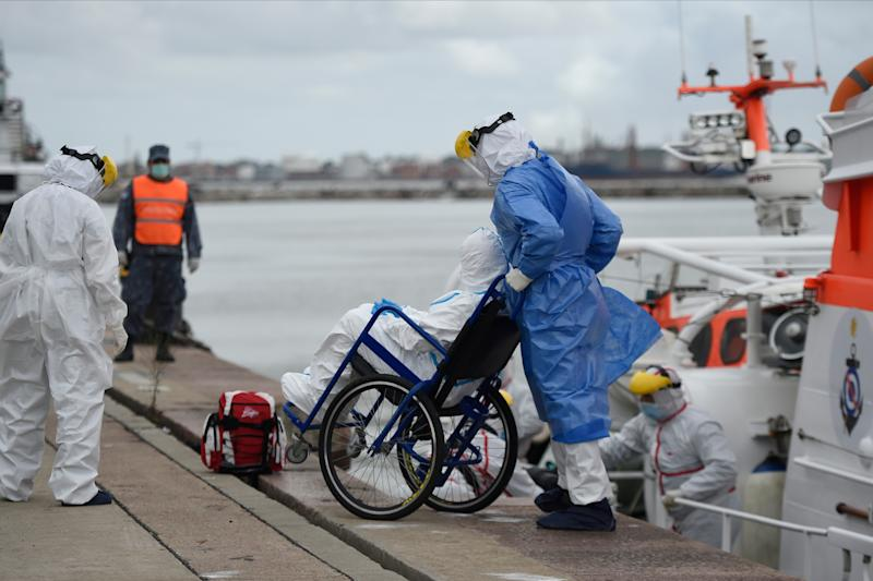 """In this picture released by Adhoc news agency medical workers transfer a sick passenger with COVID-19 from the Greg Mortimer cruise liner to an ambulance at Montevideo's port on April 8, 2020. - An Australian couple with severe symptoms of covid-19 were evacuated this Wednesday from the cruise ship Greg Mortimer, anchored for almost two weeks in front of Montevideo, and transferred to a hospital, the Uruguayan Navy reported. (Photo by Daniel RODRIGUEZ / adhoc / AFP) / Uruguay OUT / RESTRICTED TO EDITORIAL USE - MANDATORY CREDIT """"AFP PHOTO/ ADHOC / Daniel RODRIGUEZ """" - NO MARKETING NO ADVERTISING CAMPAIGNS - DISTRIBUTED AS A SERVICE TO CLIENTS (Photo by DANIEL RODRIGUEZ/adhoc/AFP via Getty Images)"""