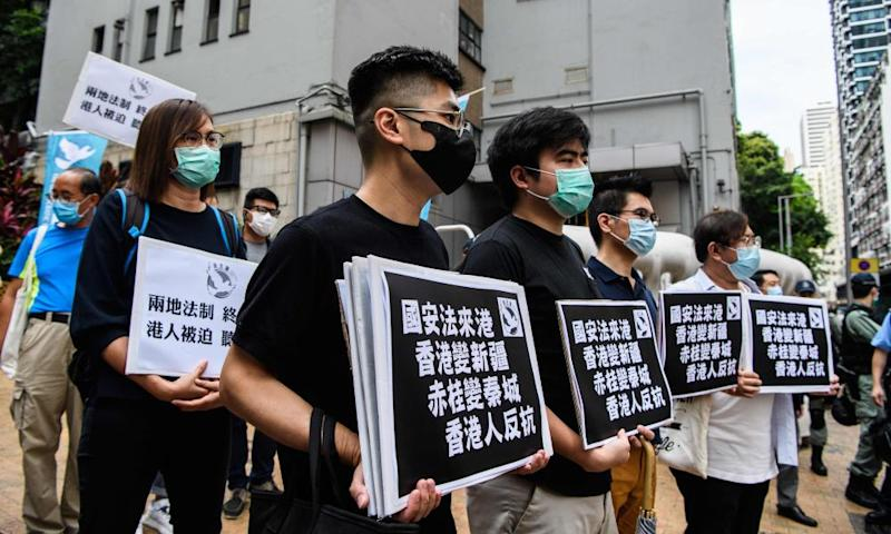 Pro-democracy protesters hold placards as they march from outside the Western Police Station to the Chinese Liaison Office in Hong Kong on 22 May.