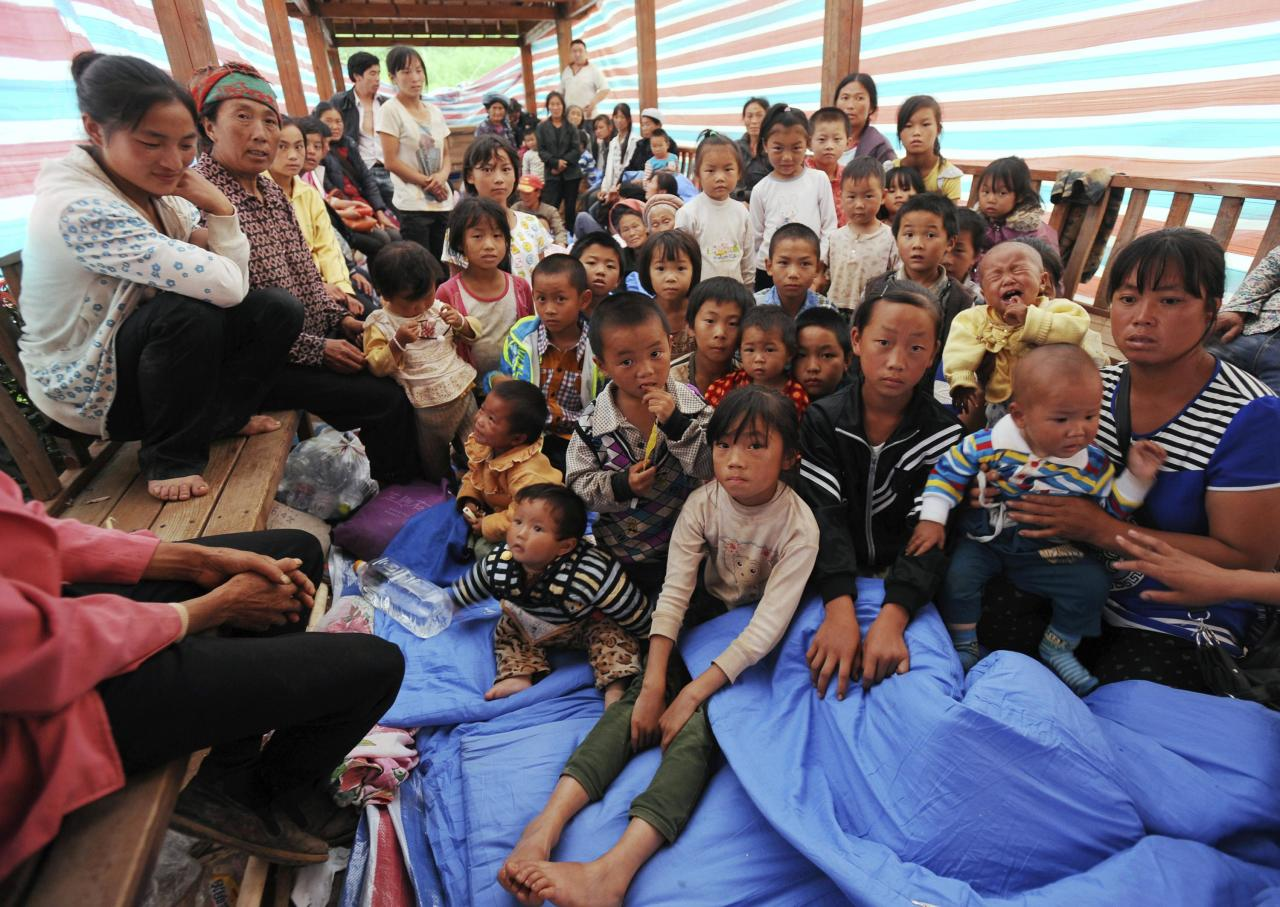 A group of villagers pose for pictures as they rest under a makeshift tent next to damaged houses, after a deadly earthquake hit Longtoushan town on Sunday, in Ludian county, Zhaotong, Yunnan province, August 4, 2014. More than 60 families are sharing the tent at the quake zone, according to local media. Picture taken August 4, 2014. REUTERS/China Daily (CHINA - Tags: DISASTER ENVIRONMENT) CHINA OUT. NO COMMERCIAL OR EDITORIAL SALES IN CHINA
