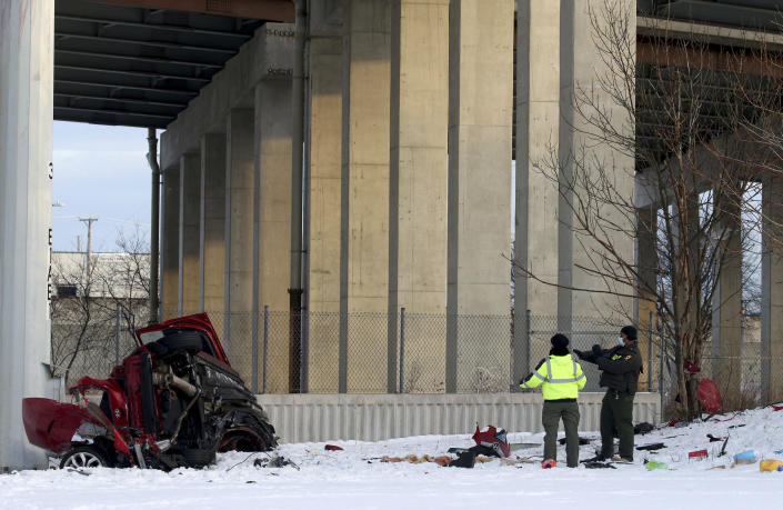 State police officers investigate the scene of a fatal crash Friday, Feb. 12, 2021 in Chicago. Police say some people were killed and others were seriously injured when their vehicle hit a concrete wall along a Chicago expressway and plunged off the highway onto a street 50 feet below. (Antonio Perez /Chicago Tribune via AP)