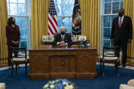 Vice President Kamala Harris, left, and Secretary of Defense Lloyd Austin, right, listen as President Joe Biden speaks before signing an Executive Order reversing the Trump era ban on transgender individuals serving in military, in the Oval Office of the White House, Monday, Jan. 25, 2021, in Washington. (AP Photo/Evan Vucci)