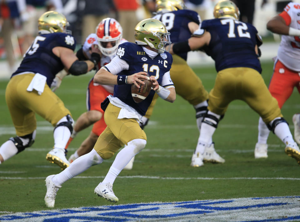 Notre Dame quarterback Ian Book (12) looks for a receiver during the first half of the Atlantic Coast Conference championship NCAA college football game against Notre Dame, Saturday, Dec. 19, 2020, in Charlotte, N.C. (AP Photo/Brian Blanco)