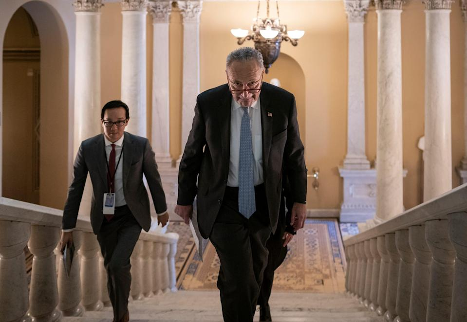 Senate Majority Leader Chuck Schumer, D-N.Y., takes the stairs to speak to reporters about progress in the impeachment trial of President Donald Trump on charges of abuse of power and obstruction of Congress, at the Capitol in Washington, Thursday, Jan. 23, 2020.