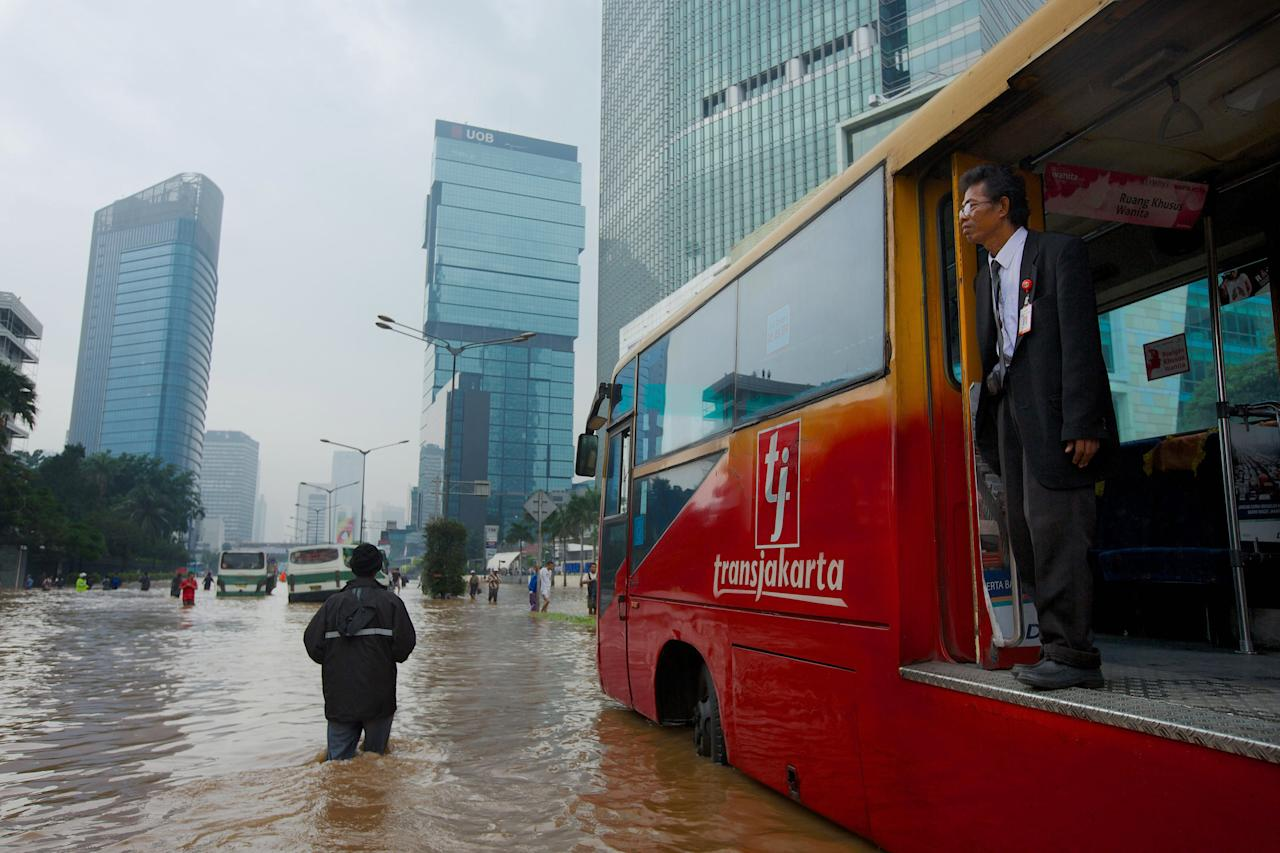 JAKARTA, INDONESIA - JANUARY 17:  People are stranded by floodwaters in Jakarta's central business district on January 17, 2013 in Jakarta, Indonesia.  Thousands of Indonesians were displaced and the capital was covered in many key areas in over a meter of water after days of heavy rain. (Photo by Ed Wray/Getty Images)