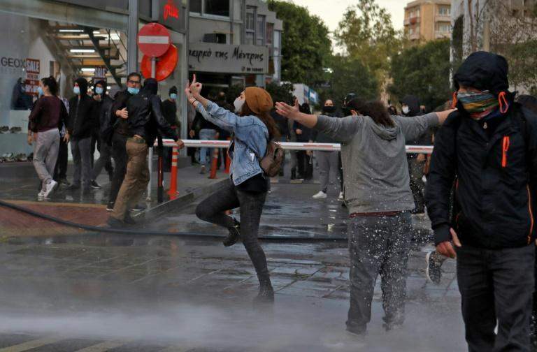 Protester Anastasia Demetriadou (C) shortly before being hit by a police water cannon