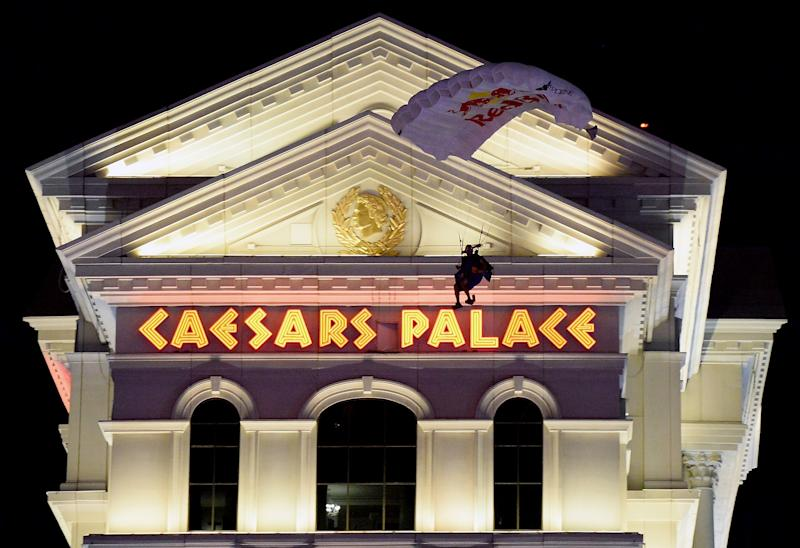 Caesars Palace sign with a skydiver coming down in front of it at night