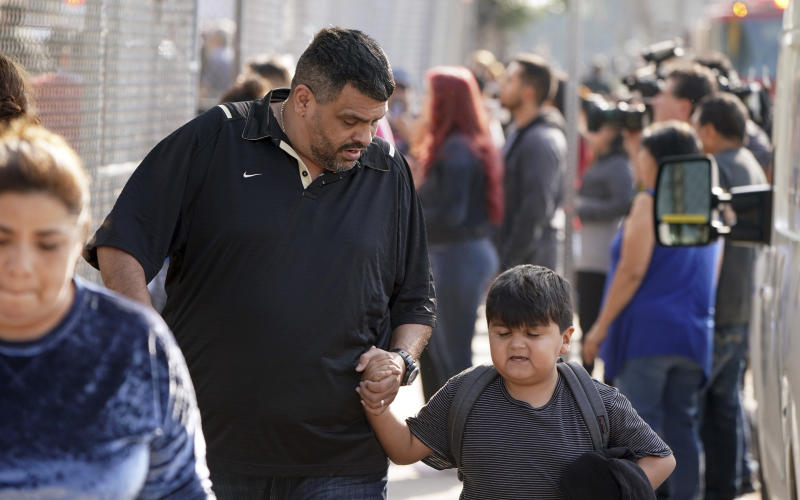 Parents and children leave Park Avenue Elementary School after multiple people were treated for jet fuel exposure in Cudahy, Calif., on Tuesday, Jan. 14, 2020. A jet returning to LAX dumped its fuel over the neighborhood and the school. Affected people at the school were treated for skin and eye irritation. No patients were transported to hospitals. (Scott Varley/The Orange County Register via AP)