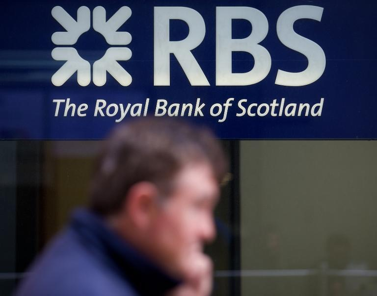 A pedestrian walks past a Royal  Bank of Scotland sign in central London on May 2, 2014