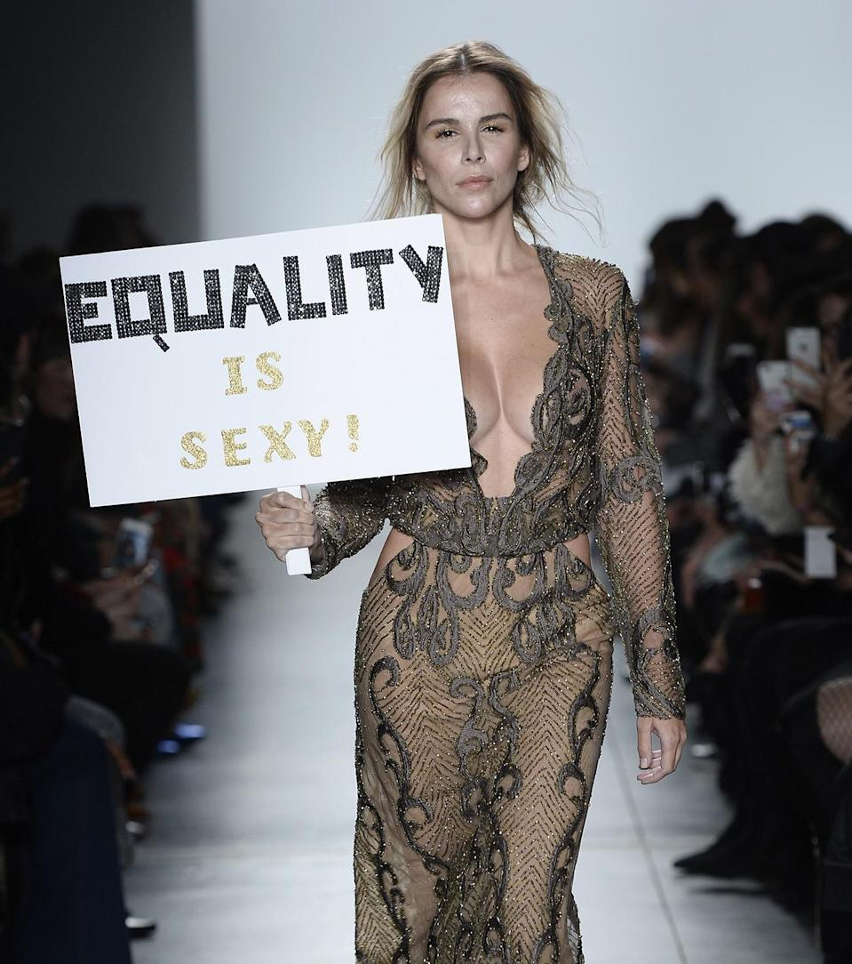 """<p>A model walks the Stella Nolasco runway show carrying a sign that reads """"Equality is sexy!"""" during New York Fashion Week. (Photo: Getty Images) </p>"""
