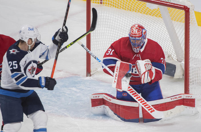 Montreal Canadiens goaltender Carey Price makes a save as Winnipeg Jets' Paul Stastny moves in for the rebound during the first period of an NHL hockey game Saturday, March 6, 2021, in Montreal. (Graham Hughes/The Canadian Press vIa AP)