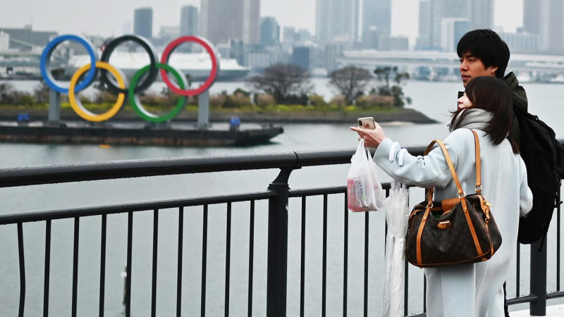 The Olympic rings in the background after as people look on.