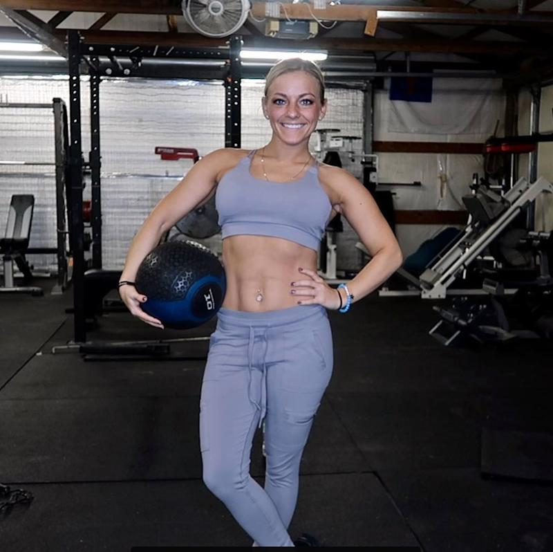 Mackenzie McKee poses in the gym wearing a sports bra
