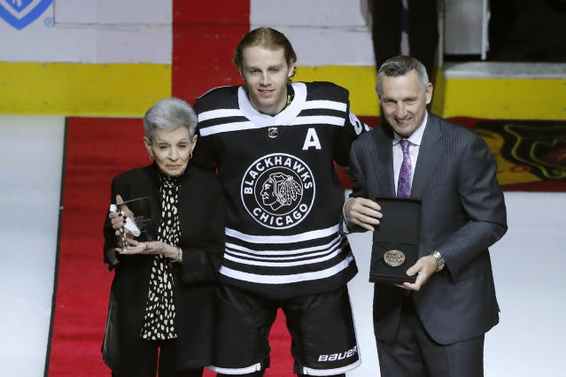 Chicago Blackhawks' Patrick Kane, center, stands with Jill Mikita, left, and Denis Savard as he is honored for his 1000th point before an NHL hockey game between the Blackhawks and Florida Panthers Tuesday, Jan. 21, 2020, in Chicago. (AP Photo/Charles Rex Arbogast)