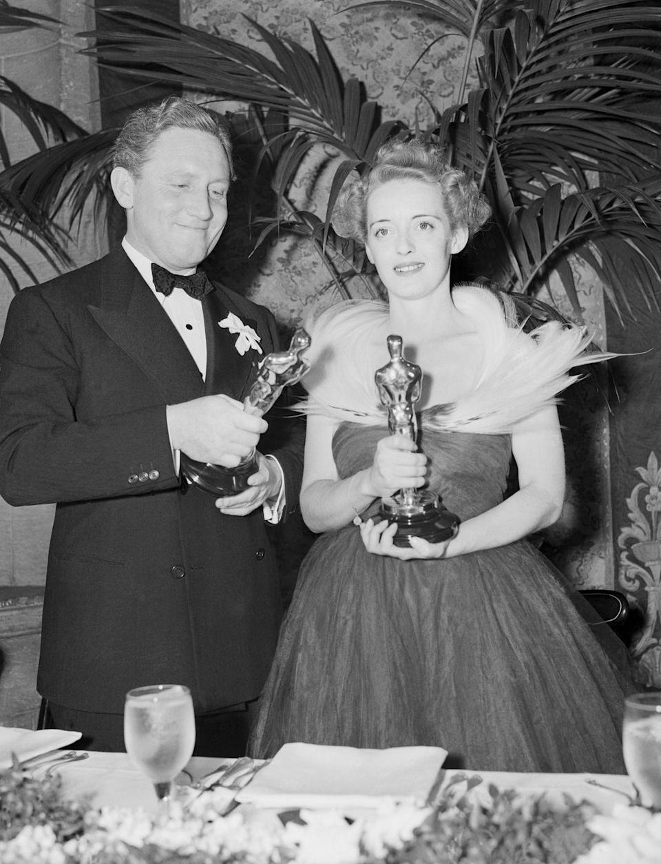 <p>Bette went for more drama with this feathered neckline and full-skirted gown. She kept her short hair in soft waves and posed with Spencer Tracy with their own respective Oscar awards.</p>