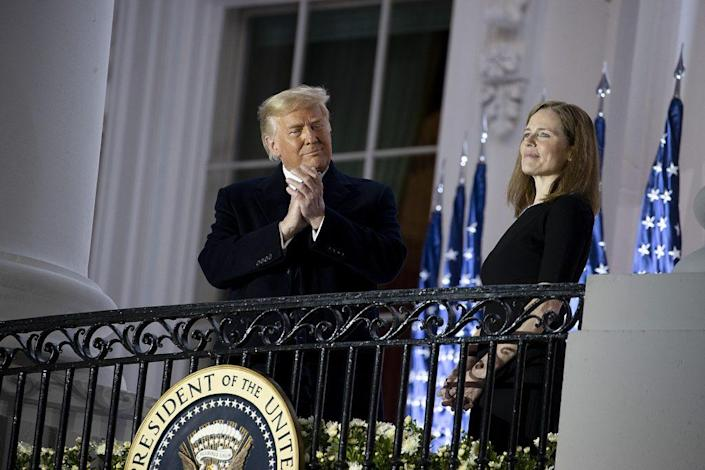 U.S. President Donald Trump stands with newly sworn in U.S. Supreme Court Associate Justice Amy Coney Barrett during a ceremonial swearing-in event on the South Lawn of the White House October 26, 2020 in Washington, DC. The Senate confirmed Barrett's nomination to the Supreme Court today by a vote of 52-48. (Photo by Tasos Katopodis/Getty Images)