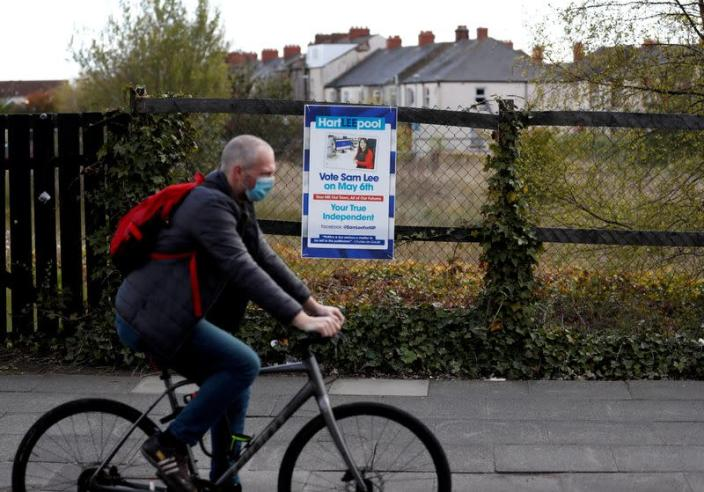 Cyclist passes an election poster ahead of tomorrow's local elections in Hartlepool