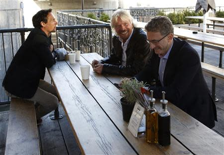 Sir Richard Branson, Founder of Virgin Group, centre, with Richard Reed, Co-Founder of Innocent Drinks, L, Kevin Horne, Chairman of the Cavendish Consortium, R, have coffee before a seminar about the Virgin StartUp scheme for young entrepreneurs at Box Park in east London, October 24, 2013. REUTERS/Olivia Harris