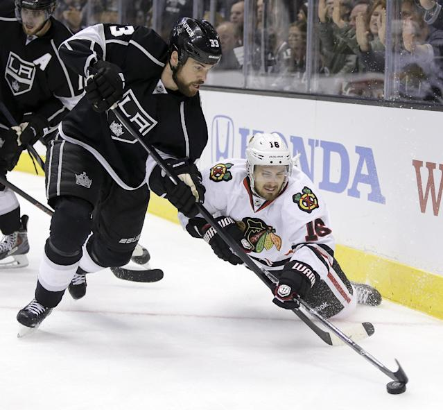 Los Angeles Kings defenseman Willie Mitchell, left, steals the puck from Chicago Blackhawks center Marcus Kruger during the third period of Game 3 of the Western Conference finals of the NHL hockey Stanley Cup playoffs in Los Angeles, Saturday, May 24, 2014. (AP Photo/Chris Carlson)