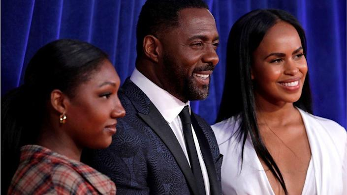Idris Elba poses with his wife Sabrina and his daughter. All three are smiling against a blue backdrop. Idris is wearing a smart suit.