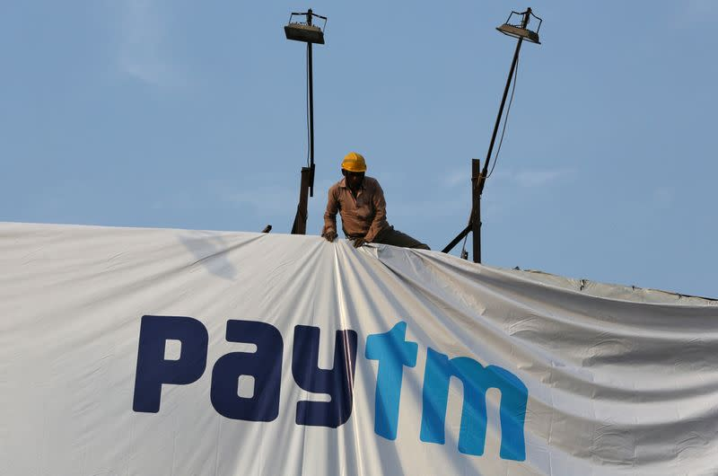 FILE PHOTO: A worker adjusts a hoarding of Paytm, a digital payments firm, in Ahmedabad