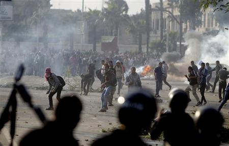 Cairo University students, who are supporters of the Muslim Brotherhood and ousted Egyptian President Mohamed Mursi, clash with riot police outside the university, in Cairo