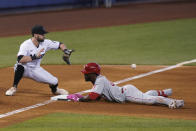 Philadelphia Phillies' Odubel Herrera, right, slides in safely into third base with a triple as Miami Marlins third baseman Jon Berti waits for the throw during the ninth inning of a baseball game, Thursday, May 27, 2021, in Miami. The Phillies beat the Marlins 3-2.(AP Photo/Wilfredo Lee)