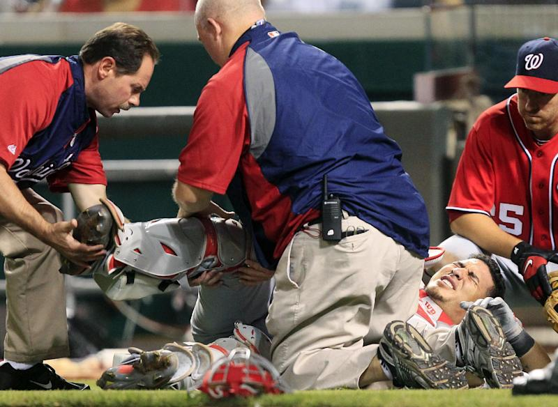 Washington Nationals catcher Wilson Ramos grimaces on the ground after he was injured in the seventh inning of a baseball game against the Cincinnati Reds, Saturday, May 12, 2012, in Cincinnati. Ramos left the game. Washington won 2-1. (AP Photo/Al Behrman)