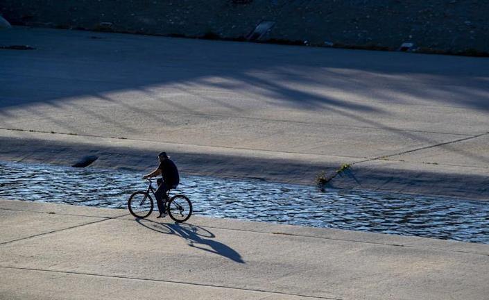 SOUTH GATE, CA - JANUARY 10: A cyclist rides in the Los Angeles River Sunday, Jan. 10, 2021 in South Gate, CA. (Brian van der Brug / Los Angeles Times)