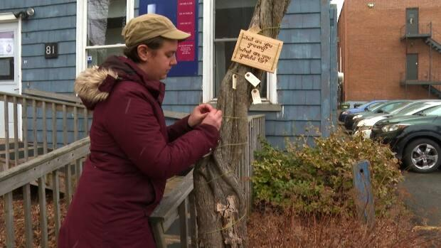 Hannah Gehrels hangs a note on the tree outside the Voluntary Resource Centre in Charlottetown. (Sheehan Desjardins/CBC - image credit)