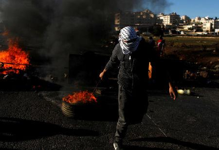 FILE PHOTO - Masked Palestinian pulls a burning tyre during clashes with Israeli troops near the West Bank city of Ramallah