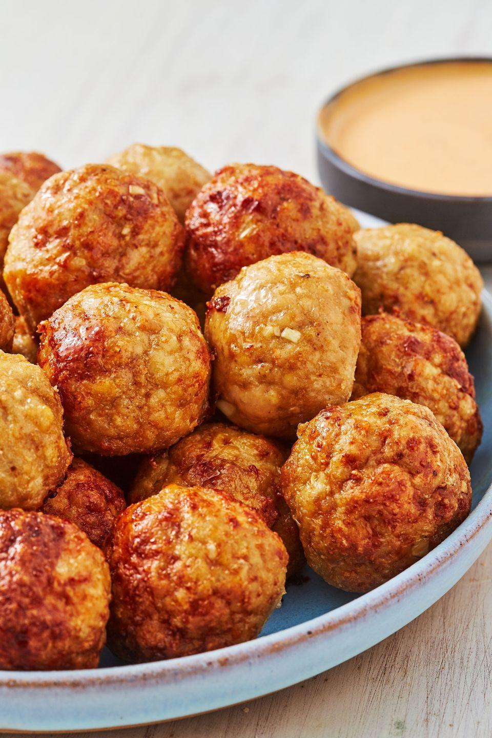 "<p>These easy meatballs can be made in the oven or air fryer. With a sweet a spicy mayo, these are perfectly shareable. </p><p>Get the recipe from <a href=""https://www.delish.com/cooking/recipe-ideas/a28580825/baked-chicken-meatball-recipe/"" rel=""nofollow noopener"" target=""_blank"" data-ylk=""slk:Delish"" class=""link rapid-noclick-resp"">Delish</a>.</p>"