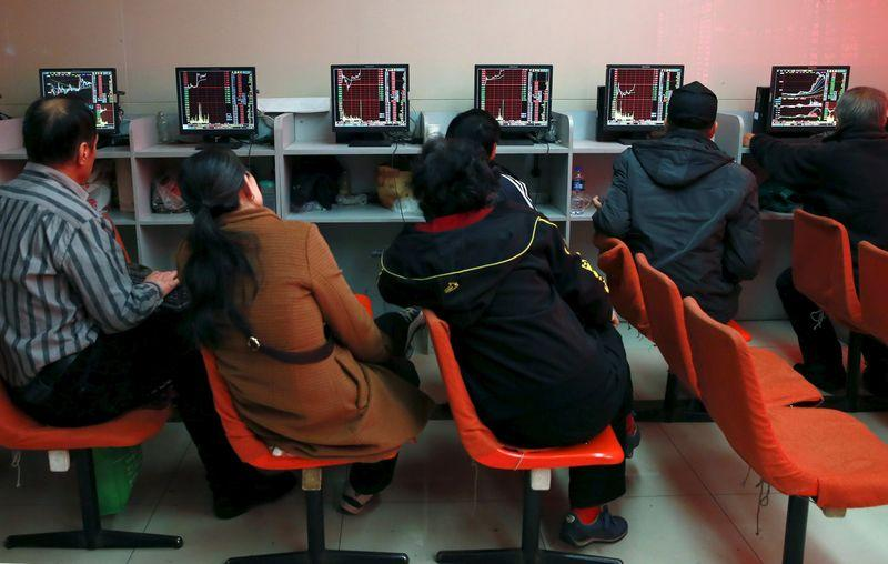 Investors look at computer screens showing stock information at a brokerage house in Shenyang