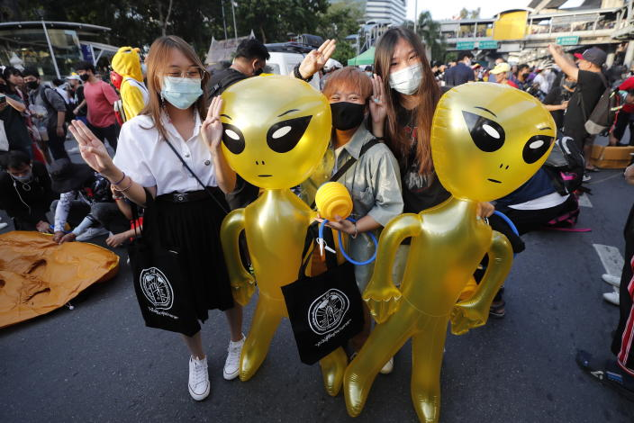 Protesters flash three-finger protest gestures while holding balloons shaped like aliens - to mock accusations that foreigners fund and direct their movement - during a rally Friday, Nov. 27, 2020 in Bangkok, Thailand. Pro-democracy demonstrators are continuing their protests calling for the government to step down and reforms to the constitution and the monarchy, despite legal charges being filed against them and the possibility of violence from their opponents or a military crackdown. (AP Photo/Sakchai Lalit)