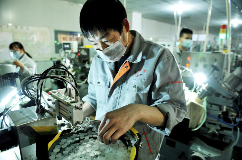 FILE - In this Feb. 23, 2020, file photo, workers make optical lenses in a factory in Dexing city in central China's Jiangxi province. China's exports fell by double digits in January and February as anti-virus controls closed factories, while imports sank by a smaller margin. (Chinatopix Via AP, File)