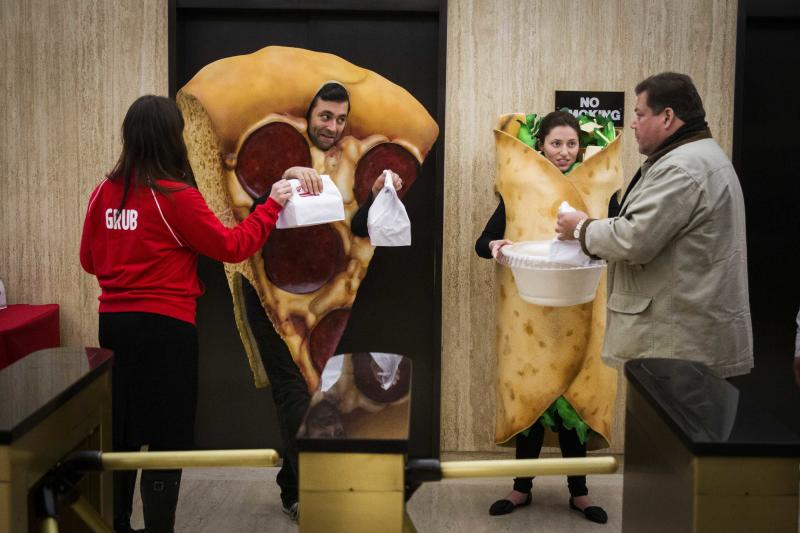 People in food-themed costumes give away donuts at the New York Stock Exchange. REUTERS/Lucas Jackson