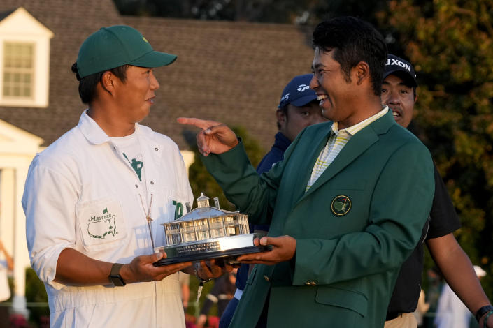 Hideki Matsuyama, of Japan, holds his trophy with his caddie Shota Hayafuji after winning the Masters golf tournament on Sunday, April 11, 2021, in Augusta, Ga. (AP Photo/David J. Phillip)