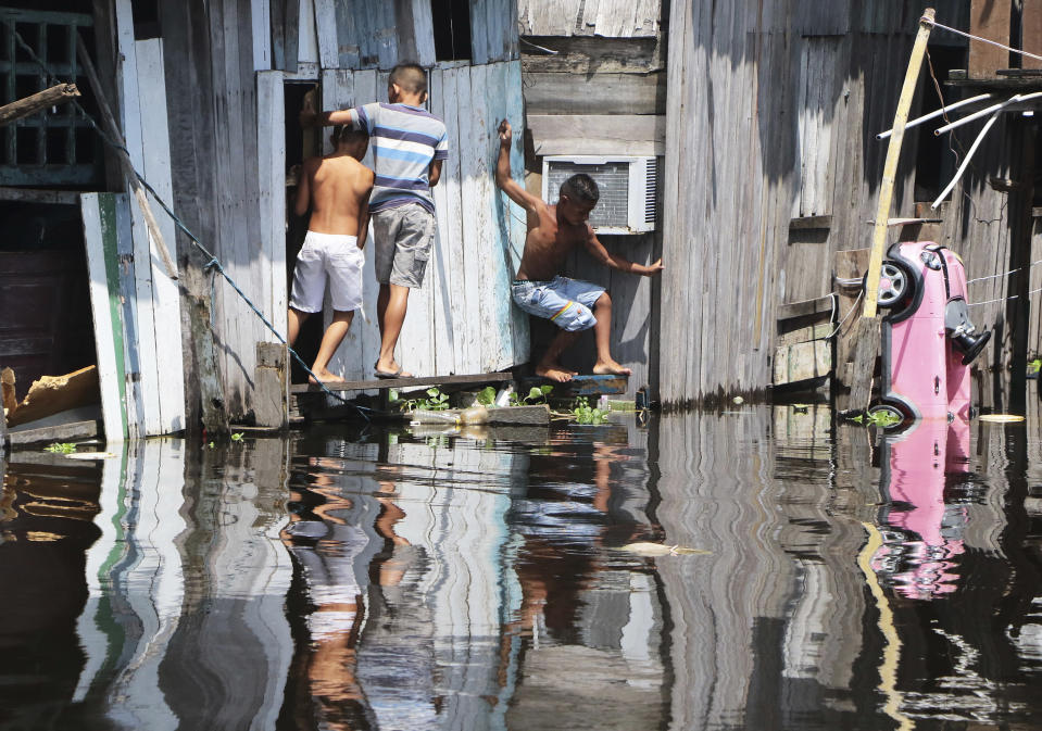 Children play outside a house, surrounded by the floodwaters of the Negro River in Manaus, Brazil, Thursday, May 20, 2021. According to official records taken by the Port of Manaus, the city is facing one of its worse floods in years, with levels not seen since 1902, making it the second-worst flood ever recorded. (AP Photo/Edmar Barros)