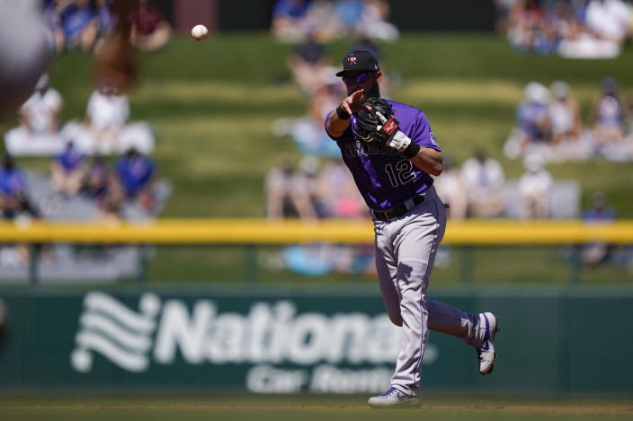 Colorado Rockies second baseman Chris Owings (12) throws to first to out Chicago Cubs' Joc Pederson during the first inning of a spring training baseball game Saturday, March 20, 2021, in Mesa, Ariz. (AP Photo/Ashley Landis)