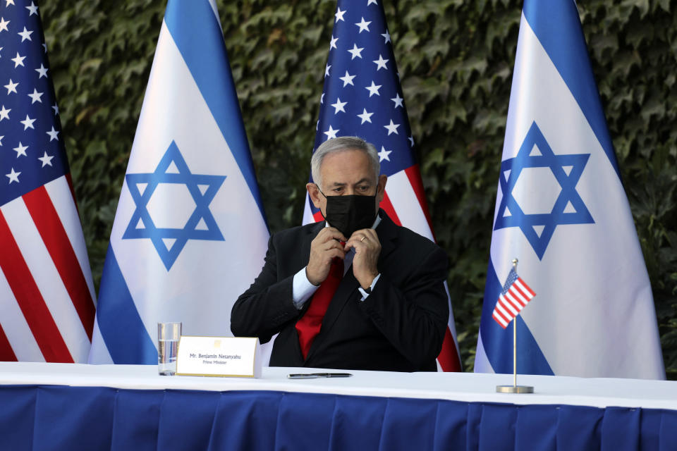 Israeli Prime Minister Benjamin Netanyahu adjusts his face mask during a ceremony to sign amendments to a series of scientific cooperation agreements with U.S. Ambassador to Israel David Friedman, at Ariel University, in the West Bank settlement of Ariel, Wednesday, Oct. 28, 2020. The United States and Israel amended the agreements on Wednesday to include Israeli institutions in the West Bank, a step that further blurs the status of settlements widely considered illegal under international law. (Emil Salman/Pool via AP)