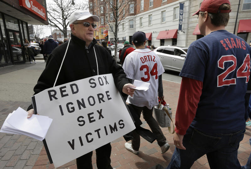 FILE - In this April 11, 2016, file photo, Robert Hoatson, left, of West Orange, N.J., hands out leaflets to baseball fans in Kenmore Square near Fenway Park, home fo the Boston Red Sox, in Boston. One of two men charged with repeatedly raping a teenage boy at New Hampshire's youth detention center in the late 1990s went on to work as a clubhouse attendant for the Red Sox, which suspended him when it learned of the allegations, the team told The Associated Press on Monday, Jan. 6, 2020. (AP Photo/Steven Senne, File)