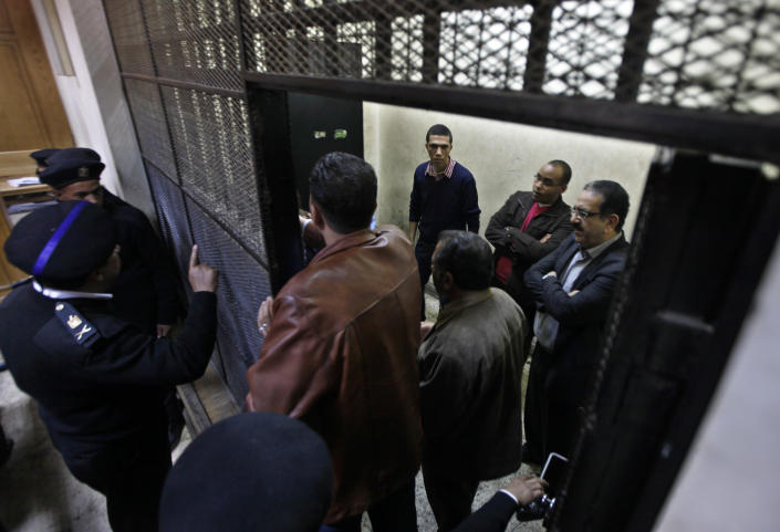 Egyptian policemen stand in front of Egyptian employees of several pro-democracy groups charged with using foreign funds to foment unrest during their trial in Cairo, Egypt, Sunday, Feb. 26, 2012. Egypt went forward with a trial Sunday that has plunged relations with the U.S. into the deepest crisis in decades, prosecuting 16 Americans and 27 other employees of pro-democracy groups. (AP Photo/Khalil Hamra)