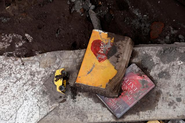 <p>Books and a toy lie on the ground at a house affected by the eruption of the Fuego volcano in San Miguel Los Lotes in Escuintla, Guatemala, June 8, 2018. (Photo: Carlos Jasso/Reuters) </p>