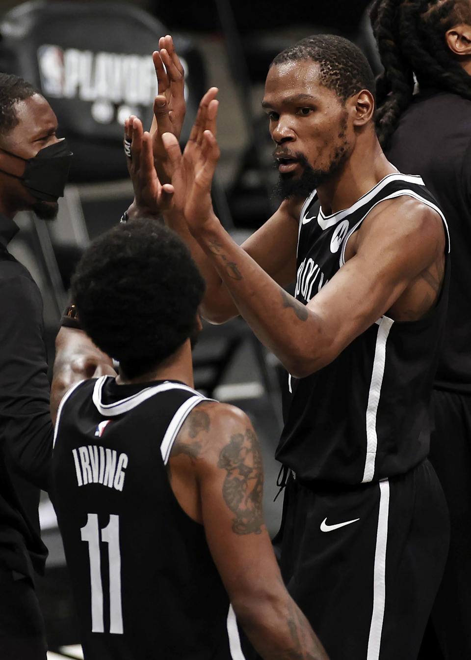 Brooklyn Nets forward Kevin Durant high-fives Kyrie Irving (11) during the second half of Game 1 of the team's NBA basketball second-round playoff series against the Milwaukee Bucks on Saturday, June 5, 2021, in New York. The Nets won 115-107. (AP Photo/Adam Hunger)