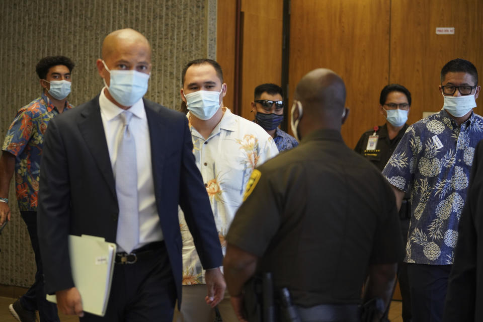 Defense attorney Thomas Otake, front left, walks into Judge William Domingo's courtroom as defendants Honolulu Police Officers Zachary Ah Nee, center, behind Otake; Christopher Fredeluces, background center; and Geoffrey Thom, far right, enter court, Tuesday, July 20, 2021, in Honolulu. The judge was scheduled to hear from witnesses to determine whether there is probable cause for murder and attempted murder charges against the three Honolulu police officers in a shooting that killed a 16-year-old Micronesian boy. (Cory Lum/Honolulu Civil Beat via AP, Pool)
