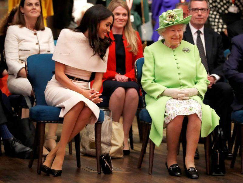 Amy Pickerell (in red) sat just behind Meghan Markle and the Queen as they visited the Storyhouse Theatre in Cheshire. [Photo: Getty]