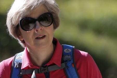 FILE PHOTO: Britain's Prime Minister Theresa May walks in a forest at the start of a summer holiday in the Alps, in Switzerland