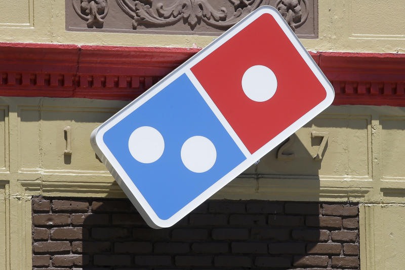 In this Monday, July 15, 2019 photo a customer departs a Domino's location holding food items, in Norwood, Mass. Domino's Pizza Inc. reports earns Tuesday, July 16. (AP Photo/Steven Senne)